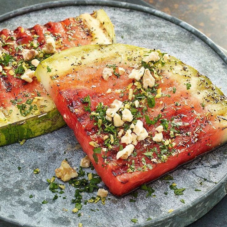 """Welcome to the grill, watermelon. Marinate these thick-cut """"steak"""" fruit slices in a mixture of white balsamic vinegar, lemon juice and rosemary. Grill watermelon slices and top 'em with a gremolata of walnuts, lemon zest and fresh parsley for knock-the-grill-tongs-out-of-your-hand taste."""