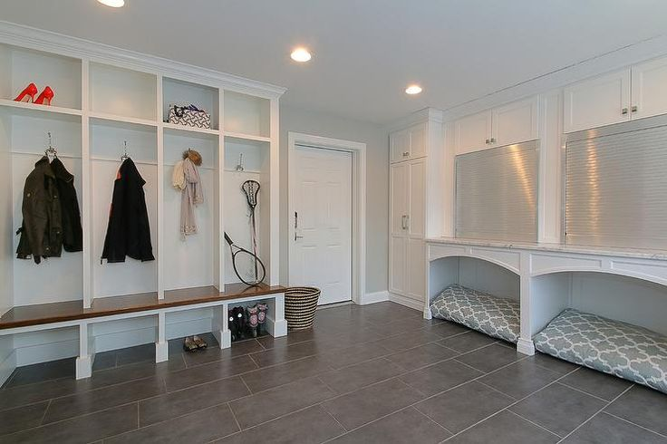 Amazing mudroom features a wall of built-in open lockers, one for each family member, situated across from side by side built in desks with aluminum garage doors over built-in dog beds accented with gray quatrefoil dog beds atop gray staggered tiled floors.