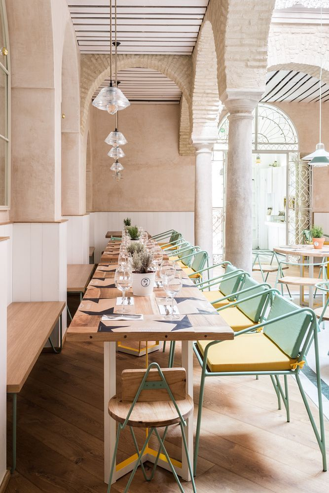 Restaurant Dining Chairs | Beautiful industrial style restaurant with mint green and pastel yellow dining chairs. | Restaurant Interior #restaurantinterior #restaurantinteriors