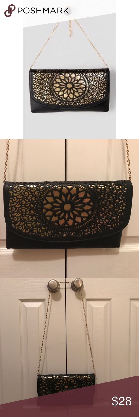 "Laser Cut Crossbody Purse Black floral laser cut design envelope clutch with gold inlay. Zips shut and has magnetic closure. 24"" Removable gold shoulder strap. Dimensions: 12"" x 7"". Faux Leather. Inside zipper pocket. Rarely used. Melie Bianco Bags Clutches & Wristlets"