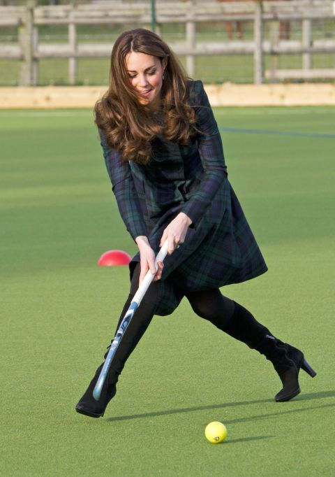 Visiting her old prep school, the Duchess dressed the part in a green tartan coat by Alexander McQueen—paired with black suede boots.