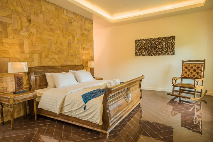 This Thai bedroom is sophisticated and modern while remaining true to its Thai roots. Loving the beautiful wooden feature wall behind the bed.