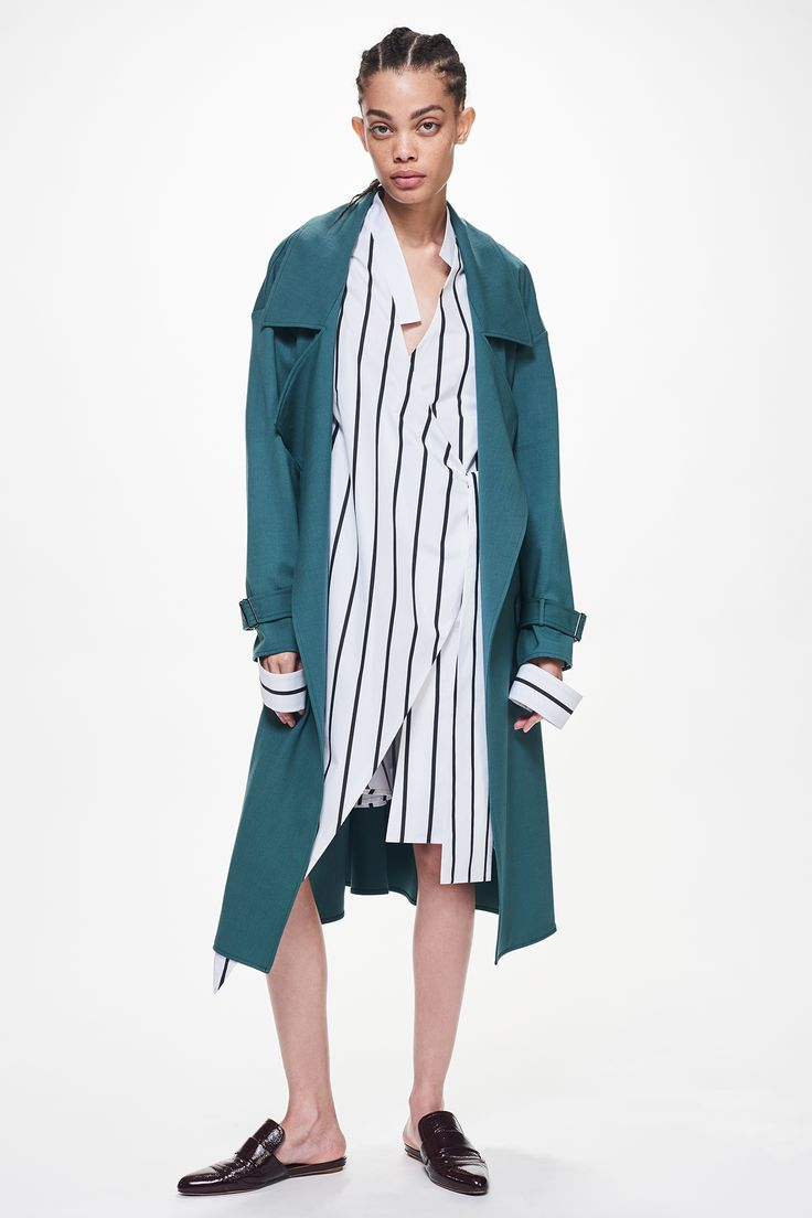 Ji Oh Navy Stripe Poplin Knee Length Cuff Dress With Diagonal Front Side Tie Closure Angled Asymmetrical Hem And Green Wool Belted Trench Coat With Silver Buckles
