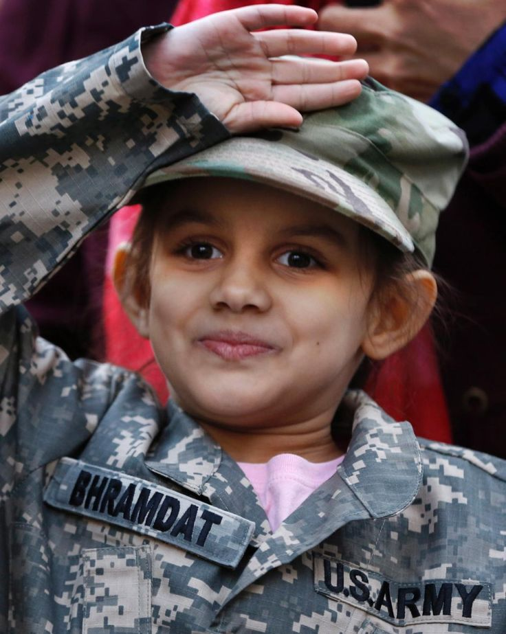 Wearing fatigues just like her mother's, Madison Bhramdat salutes as her mother is honored during a U.S. Army enlistment, reenlistment, and promotion ceremony during a Salute to Service honoring veterans ahead of Veterans' Day at the National September 11 Memorial and Museum plaza, Thursday, Nov. 10, 2016, in New York.