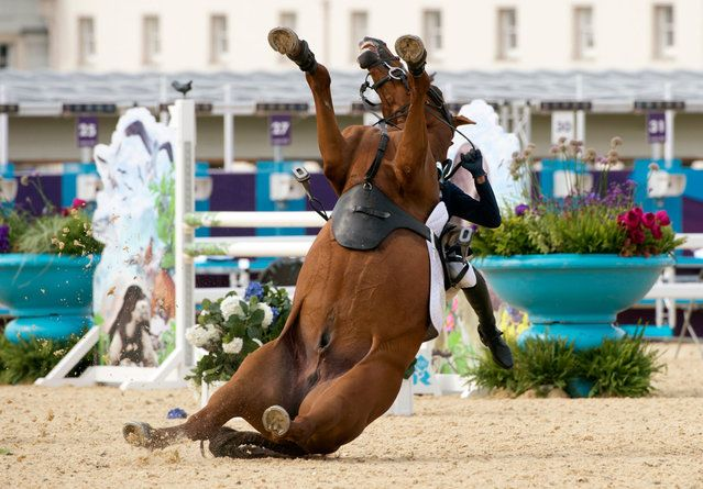 South Korea's Hwang Woojin loses control of his horse during the Show Jumping event of the Modern Pentathlon during the 2012 London Olympics at the Equestrian venue in Greenwich Park, London, on August 11, 2012. (Photo by John MacDougall/AFP)