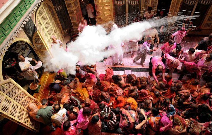 A Hindu priest throws colored powder over devotees as they celebrate the Holi festival at the Radha Krishna temple in Kolkata on March 17. H...