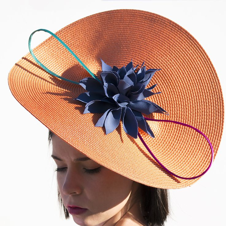 Base en espiral adornada con espagueti de raso en color fucsia y verde, y flor de crepé azul plomo hecha a mano.  Sistema de fijación: Diadema.