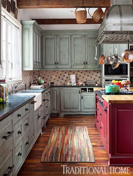 This colorful kitchen has cabinets painted soft green and an island base painted bold red. - Traditional Home ®/ Photo: Emily Minton Redfield  / Design: Dawn Bergan