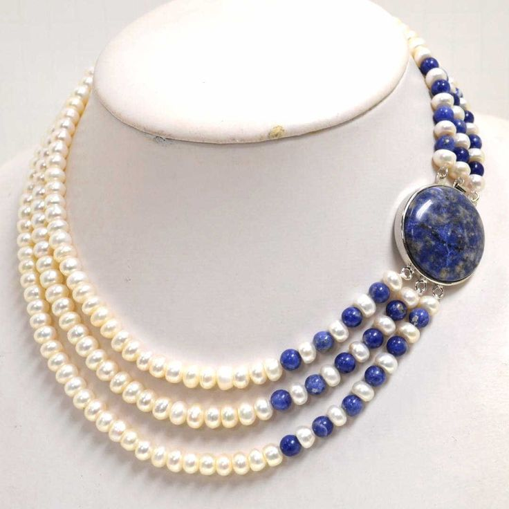 3 strand pearl necklace with 7.5mm white freshwater pearls alternating with 7mm lapis beads and silver tone clasp.