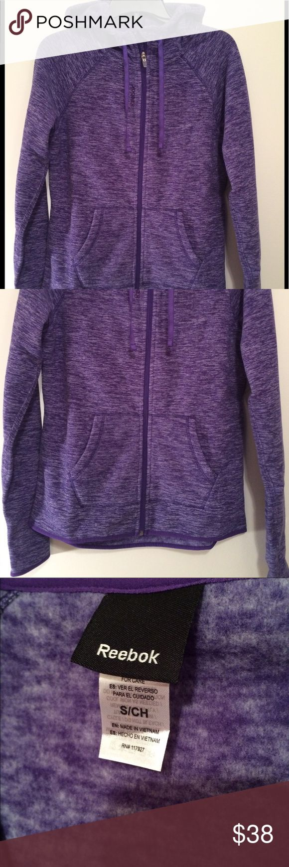 """Reebok sport small purple zip up w/thumb hole NWT Super nice purple zip up. With hood and front pockets. Heather purple with darker purple trim. Soft fabric. High low style. Approx 20"""" across and 25"""" in length and 26"""" is the back length. Thumb hole too. Reebok Jackets & Coats"""