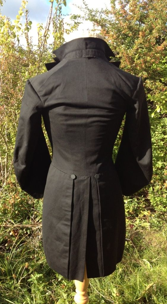 c1820-40 black broadcloth tailcoat. Broad sleeves (for riding?). Small waist. Double-breasted with black cloth covered buttons. Quilting under lapels. Lined in silk.