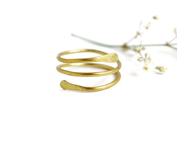 Cette bague est faite de main a martelé en laiton doré qui entoure gracieusement pour créer trois anneaux en couches.  Disponible dans toutes les tailles    Aussi disponible enveloppé avec des pierres grenat: https://www.etsy.com/listing/261031099/garnet-gold-wrap-ring-brass-garnet-ring  Si vous aimez ceci, consultez ces boucles d'oreilles qui iraient bien avec elle! https://www.etsy.com/listing/255954122/hammered-gold-triangle-studs-brass  Naviguez à travers les plus beaux bijoux qui…