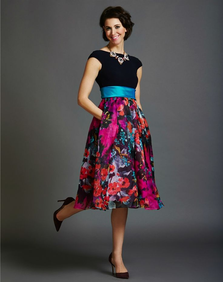 What to wear: Bridesmaid - We absolutely adore the retro-inspired silhouette of this fun Theia frock. The stretchy top is actually a deep navy and it contrasts beautifully against the bright blue belt and then pops against the vivid colours in the A-line skirt. Shop this look here: https://rentfrockrepeat.com/products/cap-sleeve-navy-tea-length-dress-with-floral-skirt