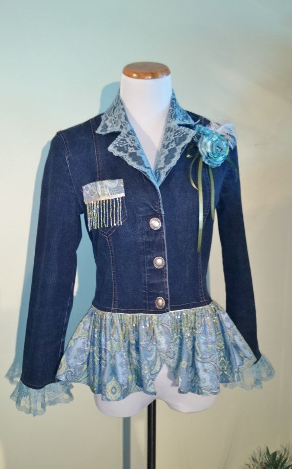 Get loads of compliments and show off your curves in this hot little tailored denim jacket. Casual enough for daytime and sexy enough for a night out!    Starting with a gently worn womens size Medium jacket, I designed a peplum of a blue-grey paisley print and matching pocket accent, and added a coordinating seed bead fringe for just a little bling. The ordinary plastic buttons were changed to classy brushed silver metal button.    The collar has an overlay of grey-blue lace and the cuffs…