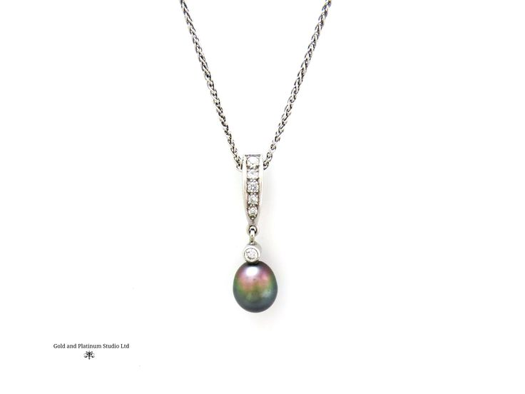 A deep black Tahitian pearl, with a line of diamonds to the bale. Very striking.