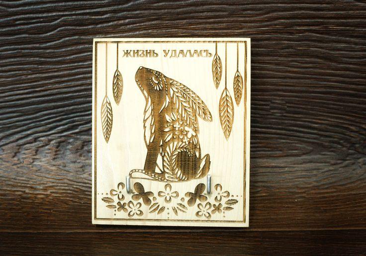 Ключница настенная с изображением кролика и надписью «Жизнь удалась» может стать хорошим подарком на новоселье для ваших друзей. Ключница изготовлена из массива сосны толщиной 1,8 см, в высоту достигает 13 см, в ширину 10,5 см. Рисунок выгравирован при помощи лазерной технологии. Подвешивается на стену при помощи, размещенной с обратной стороны металлической петли.