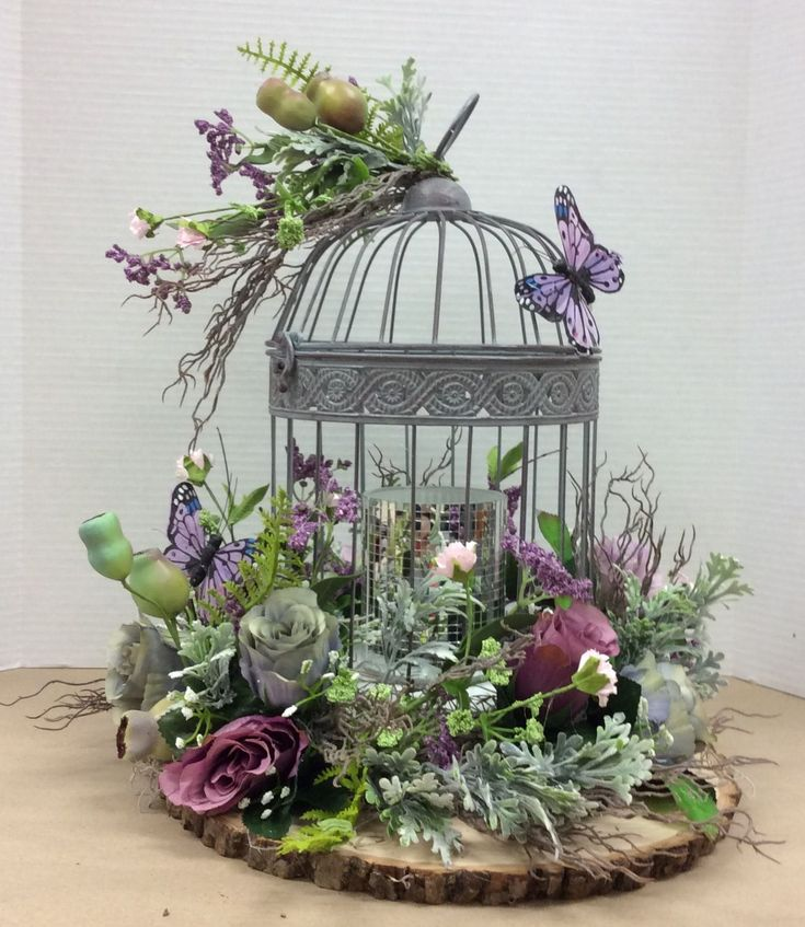 Floral design I made using wire bird cage glued to…