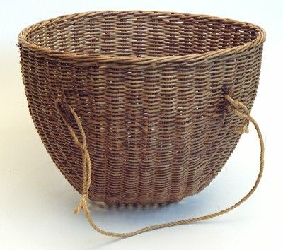36 x 42 cm 'kishie', a basket used in Shetland, Orkney and the West Highlands for carrying peat to the roads and for transporting it from the peat stacks to the fire.  It was made by D. W. McCallum of Scottish Crafts at Saint Ninian's in Stirling. It is a round basket, made of palembang cane, with a rope handle by which it would be slung over the shoulder of the wearer, usually a woman.