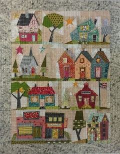 My Kinda Town quilt pattern designed by Peggy Larsen for Fiberworks features 9 whimsical paper pieced blocks In a quaint town setting! Pattern includes complete instructions for the quilt and full sized patterns. Size 42 x 54