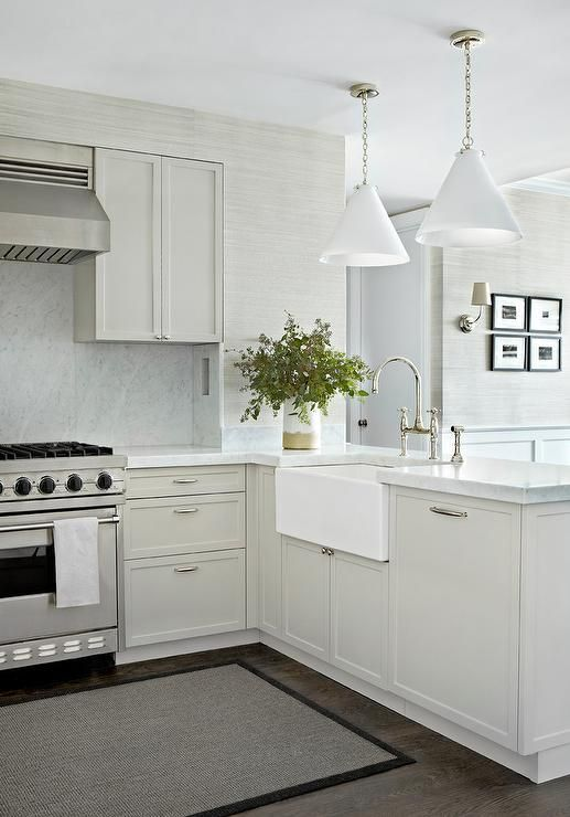 White + gray kitchen features gray shaker cabinets paired with carrera marble countertops + backsplash.