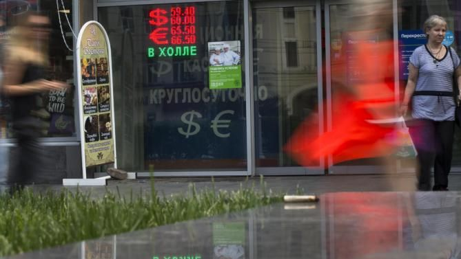 People walk past an exchange office sign showing the currency exchange rate in Moscow. The Russian ruble dropped by 2 percent on Monday, to nearly 60 rubles against the dollar.