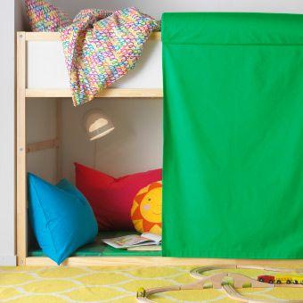 Grön gardin med kudde högst upp, hänger på sidan av en våningssäng.