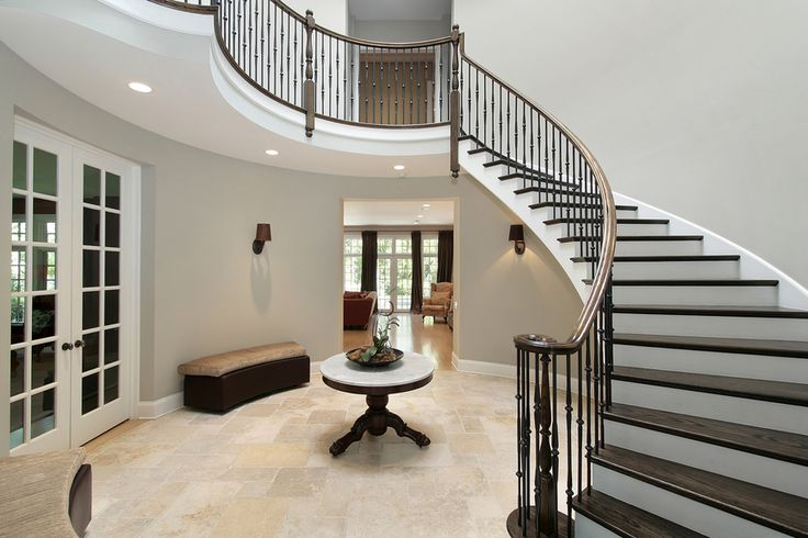 Circular entrance hall with arched dark wood stairs landing