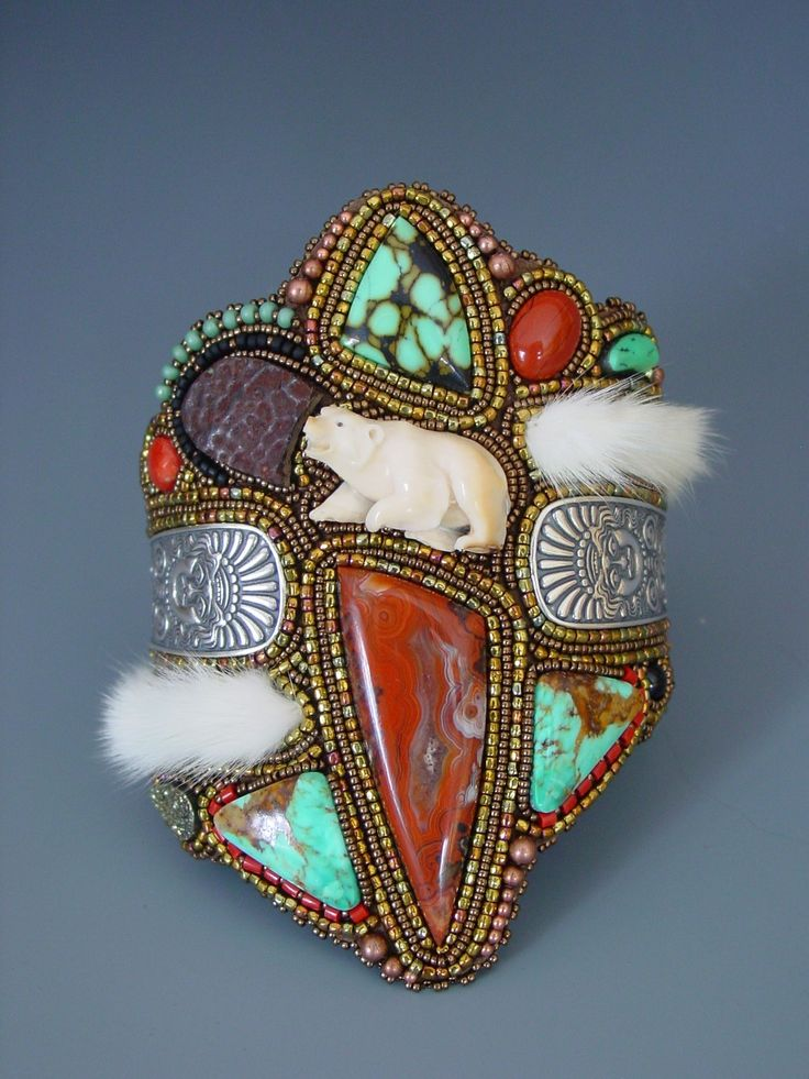 Cuff | Heidi Kummli.  Carved mammoth bone bear, 6 turquoise cabs, red jasper, coral, fossilized tortoise shell, 2 bronze eagle feathers, silver spoon handles, two ermine tails, onyx, pyrite, and lots of glass beads.