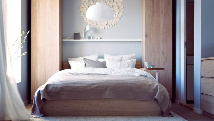 Cozy bedroom with soft bedlinens and convenient storage. Shelf above bed and storage on the side. Could maybe use the entertainment center shelves or green glass cabinet from IkEA. ?