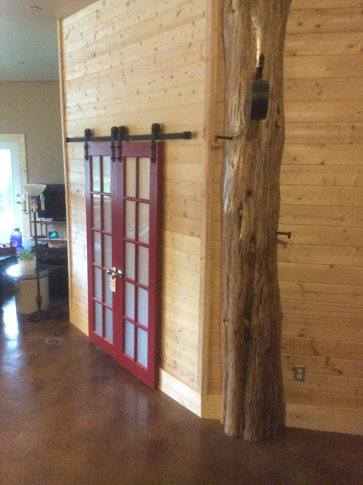 Garage conversion - we reclaimed French doors and used them for sliding barn doors to bedroom. We kept a very cool peeled log from the sawmill load & used it as a feature to displays railway spike hooks and a clock.