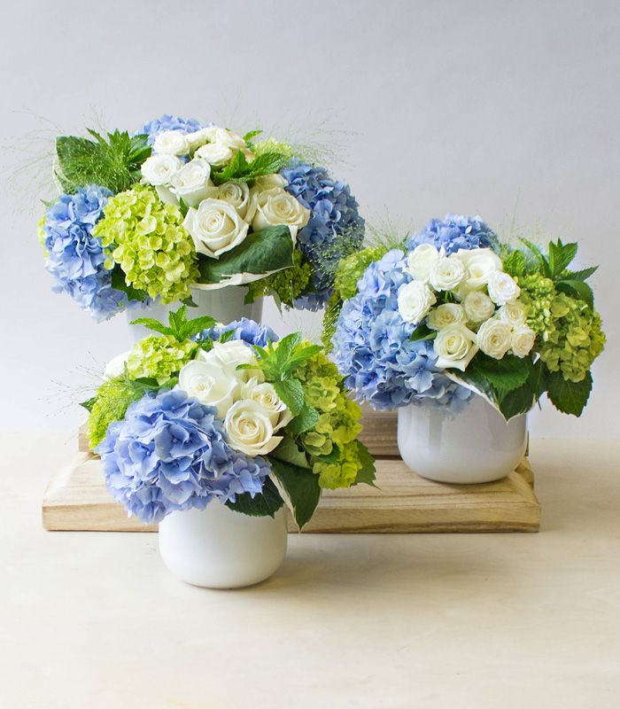 A beautiful group of floral arrangements with blue hydrangeas.  – Tischdekoration