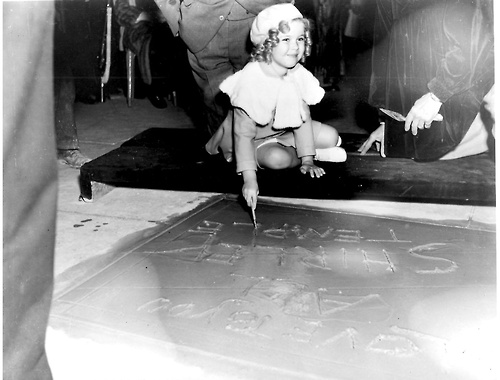 Shirley Temple signing her name at Grauman's Chinese Theatre.