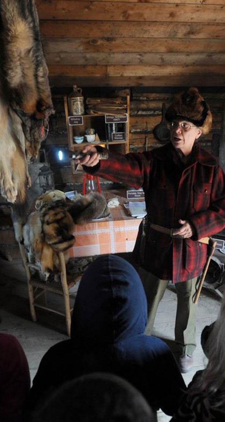 Suellyn Wright Novak channels early-20th-century Hope-area trapper, prospector and wildlife photographer Harry Johnson while showing Taku Elementary School second graders around a trapper cabin during their visit to the Pioneer School House on Wednesday, April 26, 2017, along East Third Avenue at Eagle Street. Fur and lynx pelts hang from the rafters as Novak describes daily cabin living around 100 years ago.  (Erik Hill / Alaska Dispatch News)