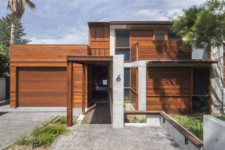 South Coast House NSW. The street elevation is arranged as a composition of timber boxes and concrete frames. The central circulation spine is introduced and gives a glimpse through to the ocean beyond.