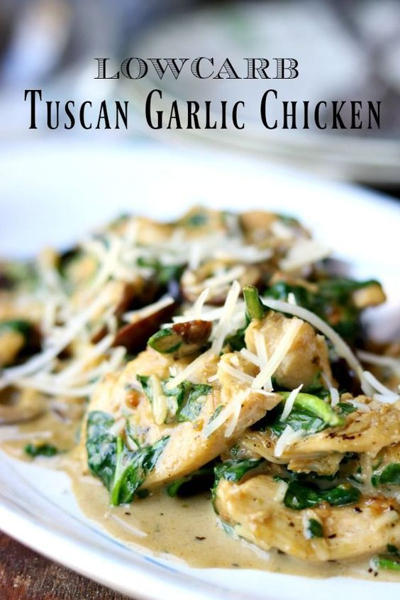 Closeup of low carb Tuscan garlic chicken, tender pieces of chicken, olives, and spinach in a creamy sauce - on a vintage white platter with a blue rim. title image