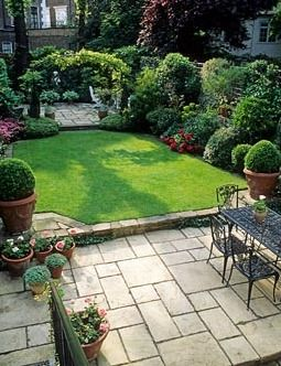 Small formal town garden with paved patio, dining table and chairs, lawn, containers, borders and arch dividing separate patio at far end of garden  like the use of the  space available.