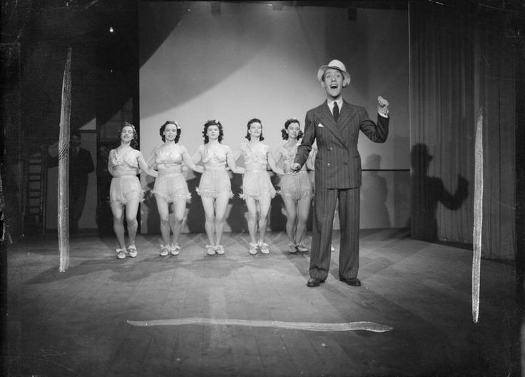 Tommy Trinder sings and dances in a British Restaurant, in an attempt to encourage the public to make use of these communal feeding centres. Behind him, six women in frilly outfits tap dance in a line.