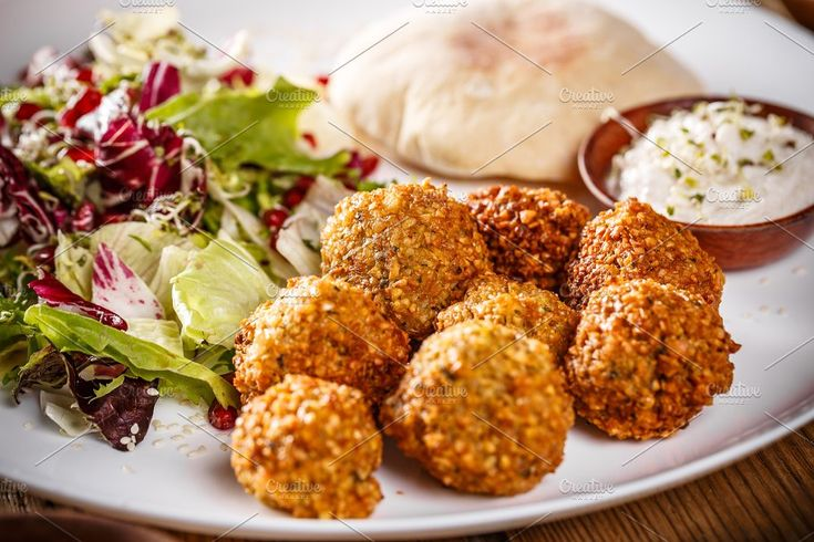 #Chickpea falafel balls  Chickpea falafel balls on a wooden desk with vegetables