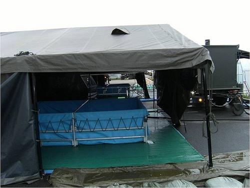 野外入浴セット2型  [構成]  トレーラ搭載器材(ボイラー,揚水ポンプ,発電機)  業務用天幕補給用,野外浴槽,シャワースタンド,貯水タンク10,000L,付属品(すのこ,脱衣かご・棚)  [入浴能力]約1200人/日  [給湯能力]5.4t/h  [湯沸時間]45分    野外において軽易に入浴を実施する装備品であり、3 1/2tトラックによりけん引する。  後方支援連隊補給隊などが装備する。
