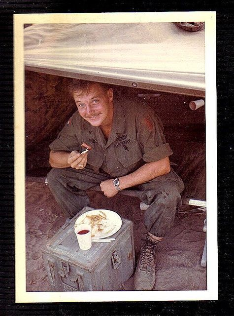 A soldier of the 1st Infantry Division eats a meal using plastic utensils, cup and plate. He wears a poplin jungle uniform with full color patches of both the 1st Infantry Division and 9th Infantry Division, as well as subdued tapes and a CIB. He appears to have his trouser legs tucked into his socks as well. Photo taken around 1968-1969.