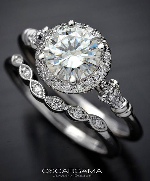 Made to Order allow 7 to 10 days Gorgeous 14kt white gold round halo engagement ring  Ring consist in a round halo with 18 diamonds around a 6.5mm Moissanite The ring is made in 14kt white gold primarily but could be customized to Pink, Yellow or Platinum  Center Stone is a 6.5mm Forever One Moissanite with a view property or 1 carat but the weight is .90ct Center stones come with Certificate from Charles & Colvard and is Laser engraved to assure quality. The diamonds are 20 total with G ...