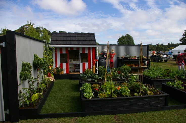 dwarf fruit trees to the left and a playhouse add a vibrant touch to this exhibitonal garden