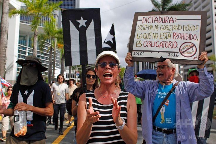 米自治領プエルトリコの首都サンフアン San Juan で、米国の51番目の州への昇格案の是非を問う住民投票に抗議してデモ行進する人々(2017年6月11日撮影)。(c)AFP/Ricardo ARDUENGO ▼12Jun2017AFP|米領プエルトリコ住民投票、「51番目の州」昇格を97%が支持 http://www.afpbb.com/articles/-/3131665