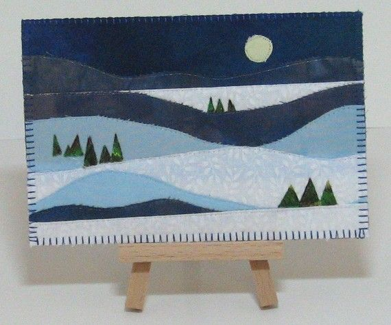 "Full Moon Serene Winter Landscape Quilted Fabric Postcard  $10 4"" x 6"" quilted fabric postcard depicting a serene winter landscape of rolling snow covered hills, suggestions of fir trees and a full moon. Blue and white fabrics are quilted following the design of the landscape in clear invisible thread. Postcard is constructed in 2 layers of fabric with a stiff interfacing in the middle. The back is white fabric with a strip of fabric representing a wooded scene"