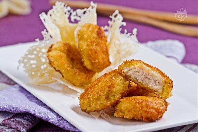 I bocconcini di pollo in crosta di parmigiano sono morbidi e croccanti pezzetti di pollo impanati, serviti in una cialda di parmigiano.
