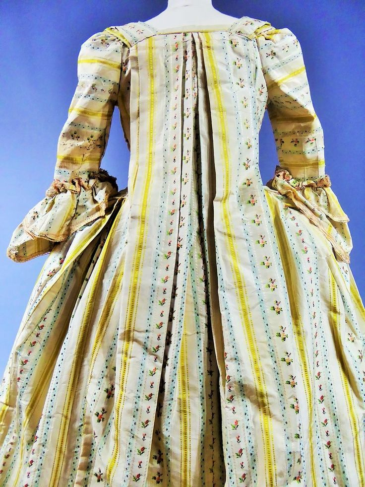 "Rear view, robe à la francaise, France, ca. 1760. ""Mexicaine"" silk taffeta with yellow stripes on cream ground alternating with stripes with small bouquets on light blue and cream ground, linen lining. Sleeve ruffles with pink trimmings."