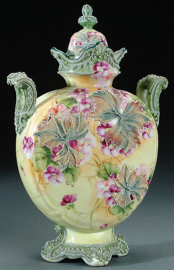 A NIPPON MORIAGE DECORATED PORCELAIN COVERED URN CIRCA 1915 WITH LARGE MORIAGE GRAPE LEAVES ON A PAINTED WILD FLOWER GROUND WITH TWO HANDLES