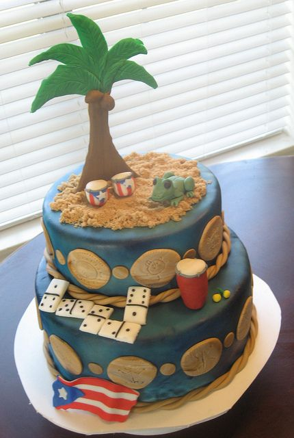 Birthday cake, covered in fondant with Taino symbols going around the cake and a coqui, bongo, conga and dominoes. Of course the Puerto Rico flag in the shape of the island.