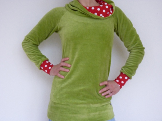 Super gemütlicher Pullover aus grünem Nicki mit einem gefütterten Schalkragen und Ärmelbündchen aus Jersey in rot mit weißen Tupfen. Die Bündchen s...
