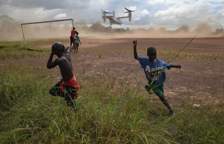 Oct. 15, 2014. Boys run from the blowing dust as a U.S. Marine MV-22 Osprey tiltrotor departs the site of an #Ebola treatment center under construction in Tubmanburg, #Liberia. JOHN MOORE—GETTY IMAGES